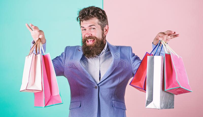 Man bearded hipster businessman formal suit carry paper shopping bags. Ready for holiday. Buy gifts for everyone. Buy. Gifts in advance. Enjoy shopping black royalty free stock photography