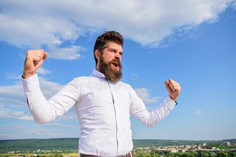 Man bearded hipster feels powerful and full of energy when reached top achievement. Man emotional enjoy freedom sky royalty free stock image