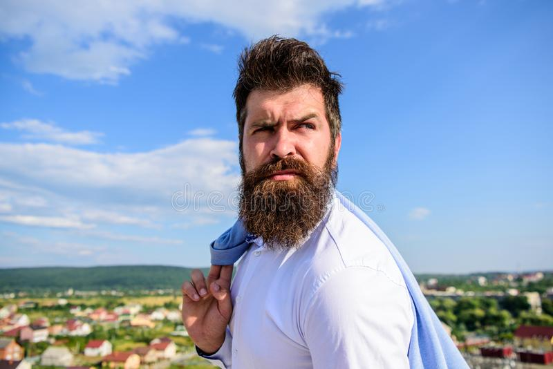 Man bearded hipster formal style look back sky background. Guy reached top but feel frustrated. Motivation and ambitions royalty free stock image
