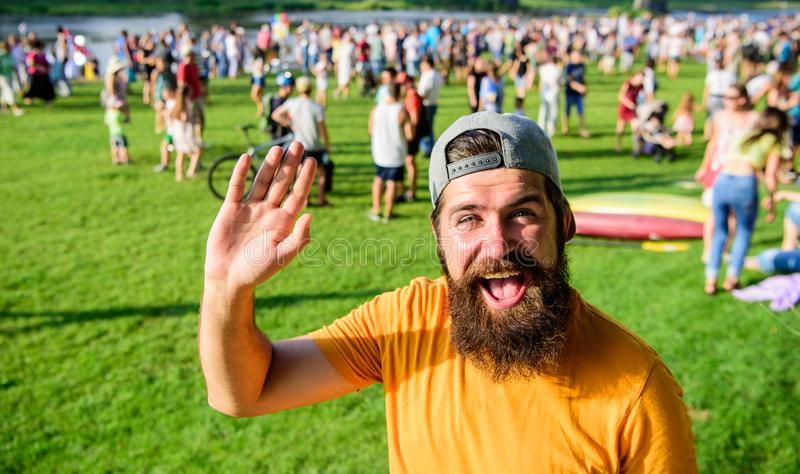 Man bearded hipster in front of crowd people green field background. Hipster in cap visiting social event picnic fest or. Festival. Urban event celebration. Man royalty free stock photos