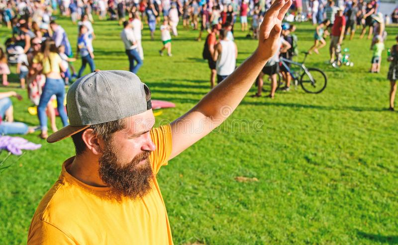 Man bearded hipster in front of crowd people green field background. Urban event celebration. Man waving hand sunny day. Outdoors. Hipster in cap visiting royalty free stock images