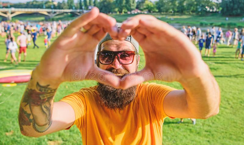 Man bearded hipster in front of crowd people show heart gesture riverside background. Hipster happy celebrate event. Picnic fest or festival. Urban event stock images