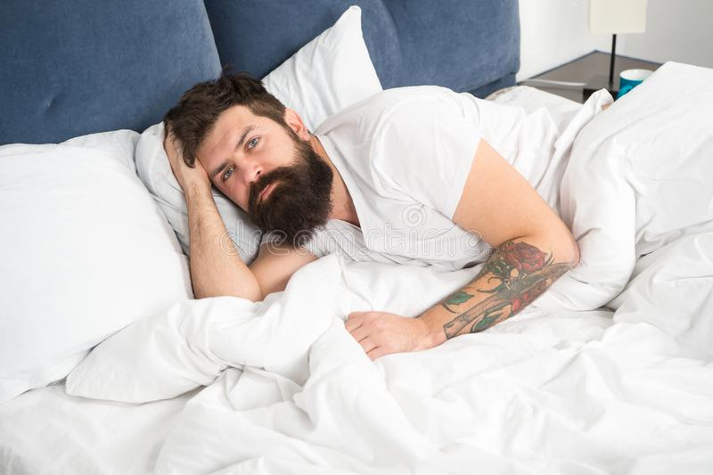 Man bearded hipster having problems with sleep. Guy lying in bed try to relax and fall asleep. Relaxation techniques. Violations of sleep and wakefulness. Need royalty free stock photography