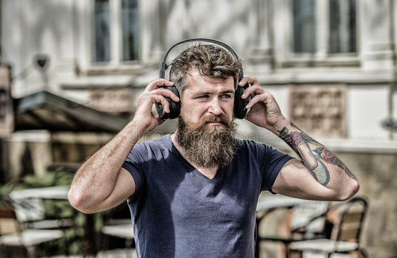 Man bearded hipster headphones listening music. Hipster enjoy excellent sound song in earphones. Walking with music stock photo