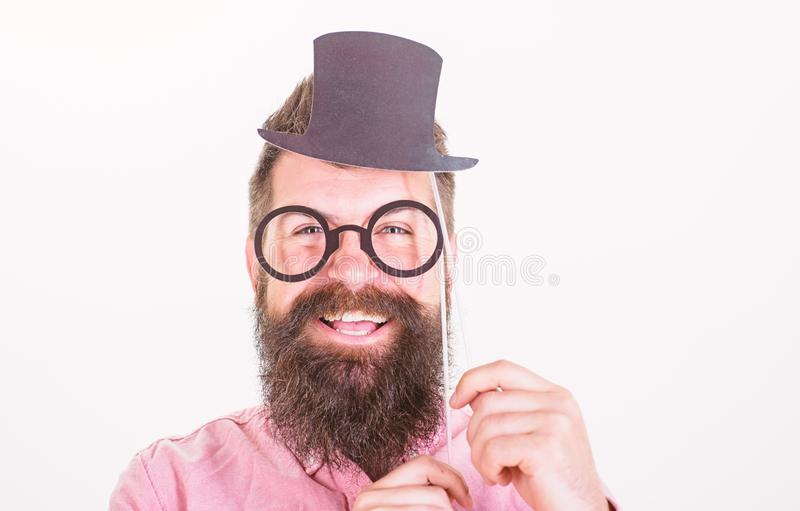 Man bearded hipster hold cardboard top hat and eyeglasses to look smarter white background. Dress affects how people see. You. Guaranteed ways appear smarter royalty free stock photography