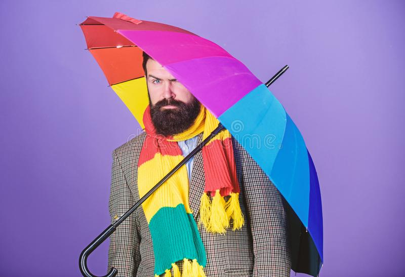 Man bearded hipster hold colorful umbrella. It seems to be raining. Rainy days can be tough to get through. Prepared for. Rainy day. Carefree and positive royalty free stock images
