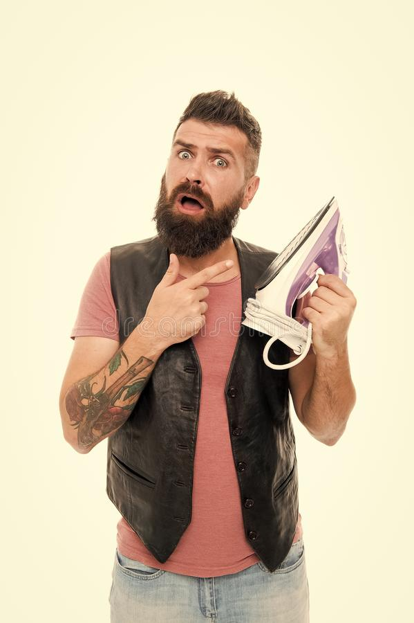 Man bearded hipster hold electric ironing tool. How iron clothes correctly. Guy with iron on white background isolated. Tailor and dry cleaning service stock photography