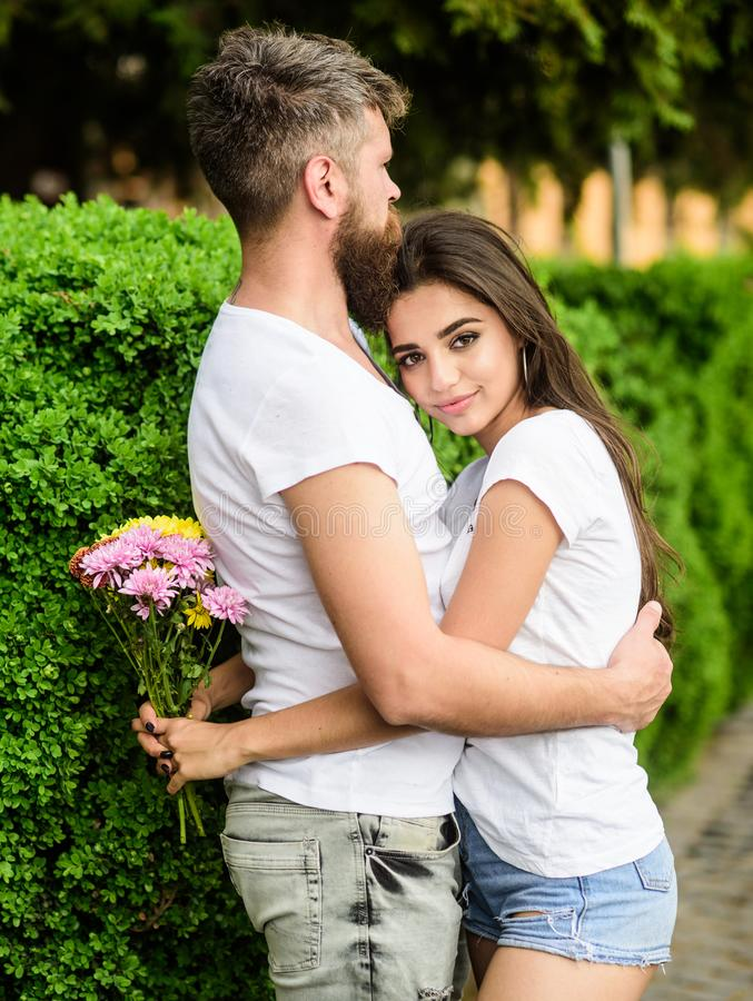 Man bearded hipster hugs woman. Man fall in love with gorgeous girl. Strong romantic feelings become true love. She royalty free stock photo