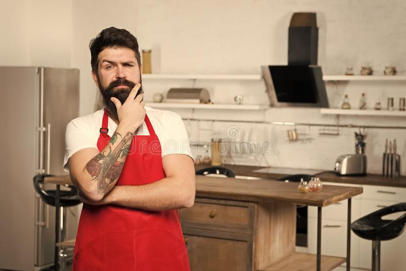 Man bearded hipster red apron stand in kitchen. Kitchen furniture store. Cooking in new kitchen. Need culinary. Inspiration. Weekend begins from tasty breakfast royalty free stock photos