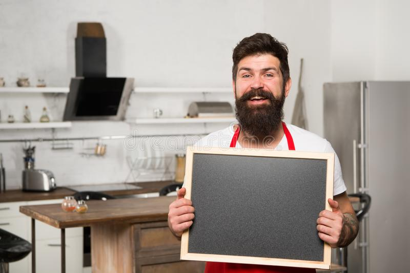 Man bearded hipster red apron stand in kitchen. Kitchen furniture store. Kitchen hacks concept. Clever ways to organize. Kitchen. Cook hold blank chalkboard stock photography