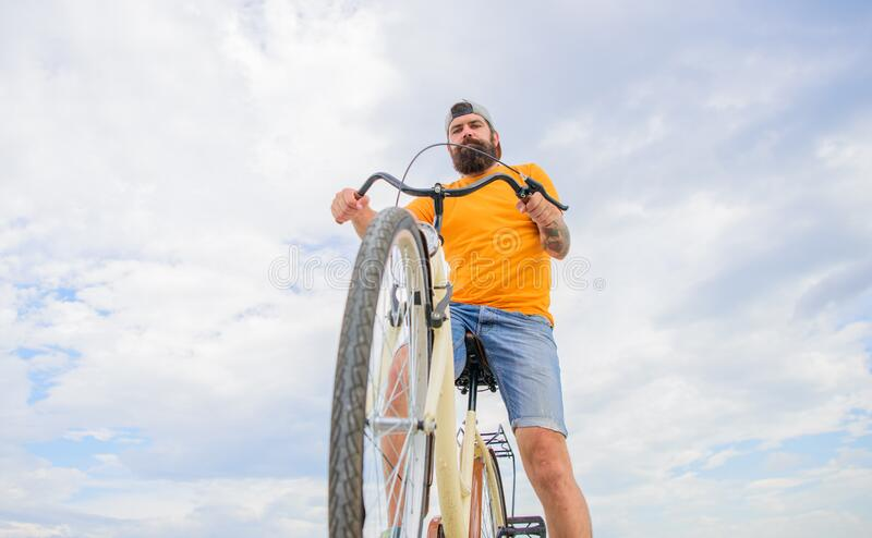 Man bearded hipster rides bicycle bottom view sky background. Modern bicycle riding culture. Optimise cycling stock image
