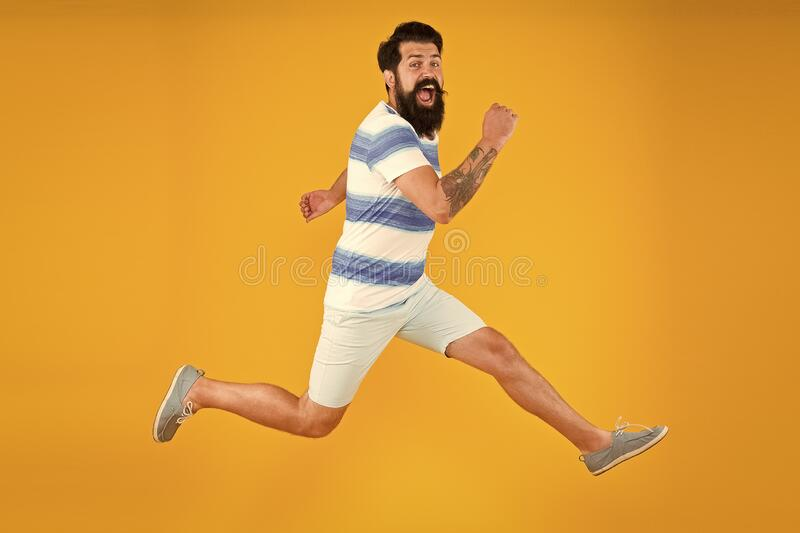 Man bearded hipster run yellow wall. Guy beard striped shirt. Freedom jump. Sale and discount. rush hour. lets go stock image