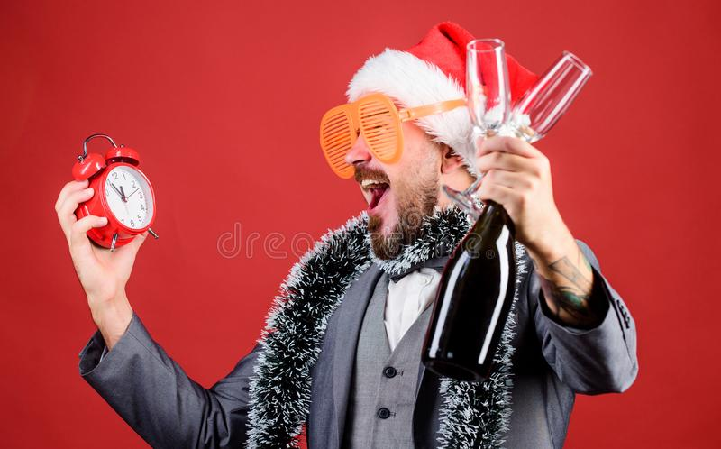 Man bearded hipster santa hat champagne bottle. alarm clock. Corporate party. Cheers concept. Join office party. Winter royalty free stock photos
