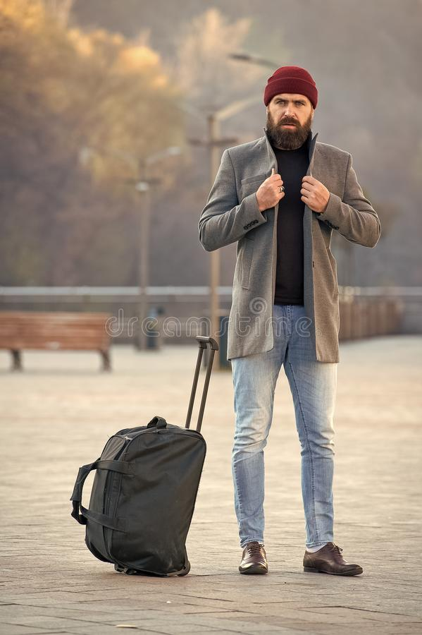 Man bearded hipster travel with big luggage bag wait for taxi bring him to hotel. Travel tips. Traveler with suitcase. Arrive travel destination. Hipster ready stock images