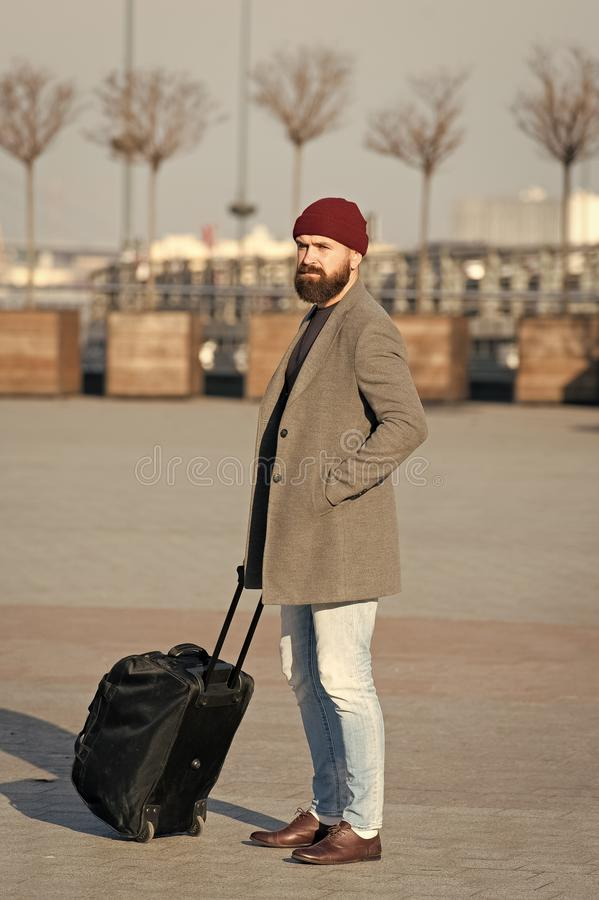 Man bearded hipster travel with big luggage bag on wheels. Let travel begin. Traveler with suitcase waiting. Transportation to airport railway station. Ready to royalty free stock photos