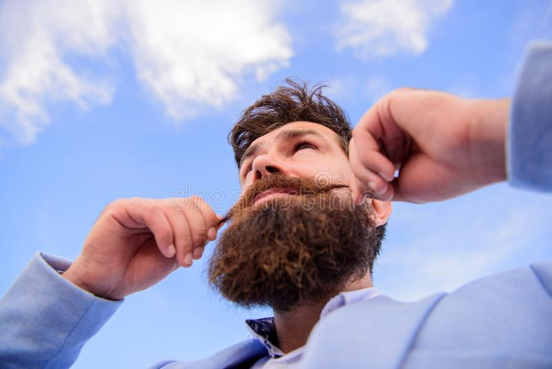 Man bearded hipster twisting mustache sky background. Ultimate moustache grooming guide. Hipster handsome attractive guy. Close up. Expert tips for growing and stock photo