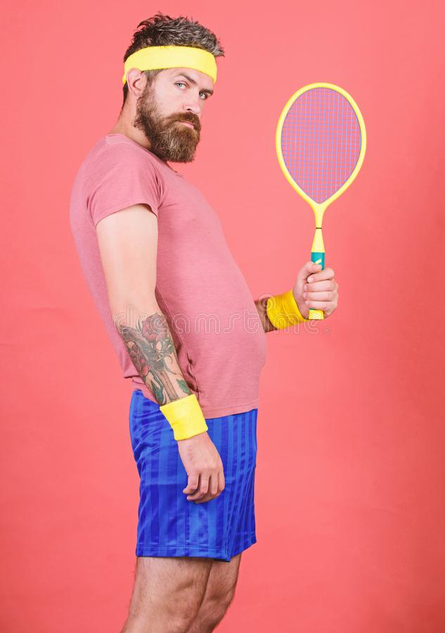 Man bearded hipster wear old school sport outfit with bandages. Tennis can be an effective way to lose weight. Athlete. Hold tennis racket in hand on red royalty free stock photo