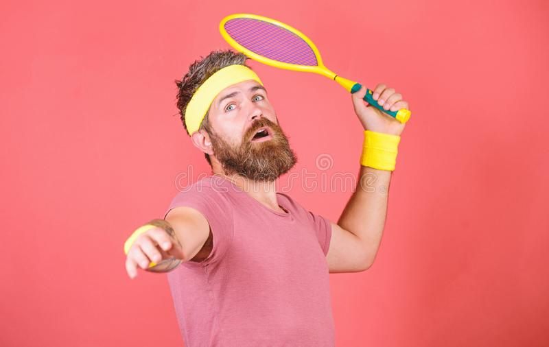 Man bearded hipster wear sport outfit. Tennis player retro fashion. Tennis sport and entertainment. Athlete hipster hold. Tennis racket in hand red background stock images