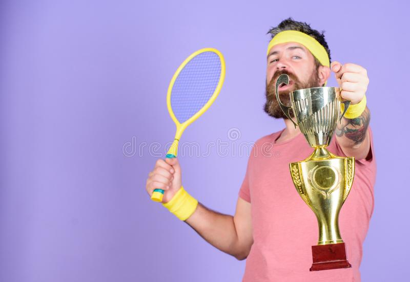 Man bearded hipster wear sport outfit. Tennis player win championship. Athlete hipster hold tennis racket and golden. Goblet. Win tennis game. No player can stock photo