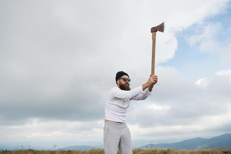 Man bearded lumberjack in sunglasses, hat raise axe stock photo