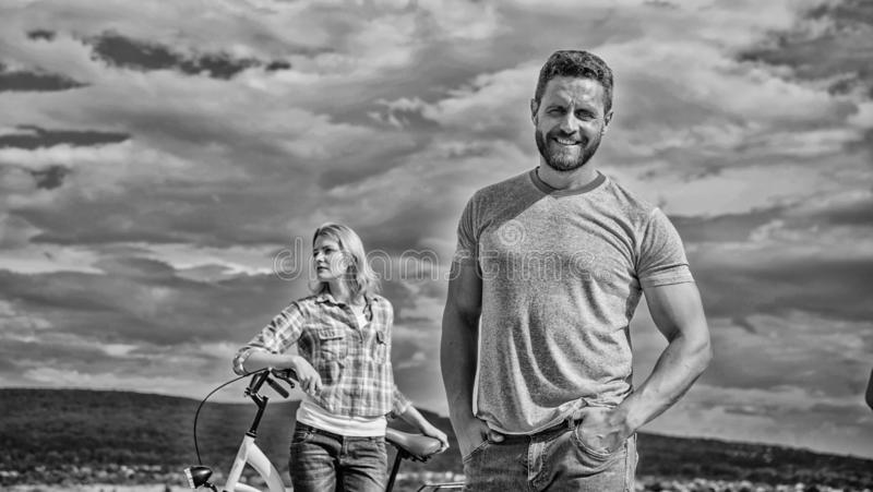 Man bearded macho posing confidently in front of shy girl with bike. Cycling instructor concept. Lady dreams he teach royalty free stock photography