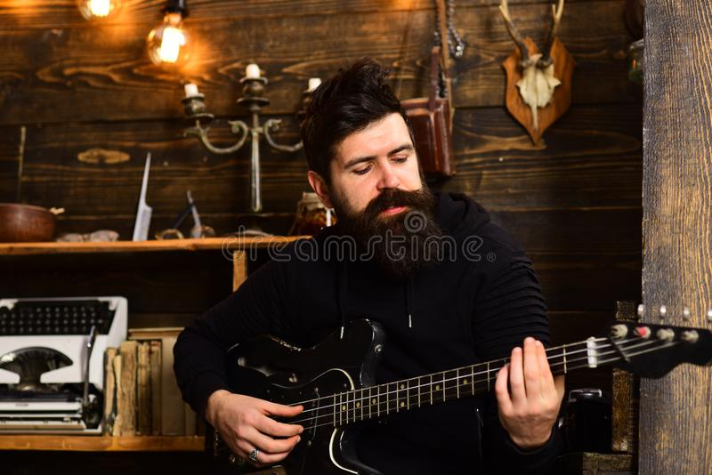 Man bearded musician enjoy evening rehearsing performance at home, wooden background. Boost your skills. Guy in cozy stock images
