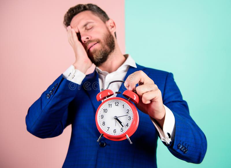 Man bearded sleepy businessman hold clock. Stress concept. Mature man beard tired because of work. Businessman has lack royalty free stock image