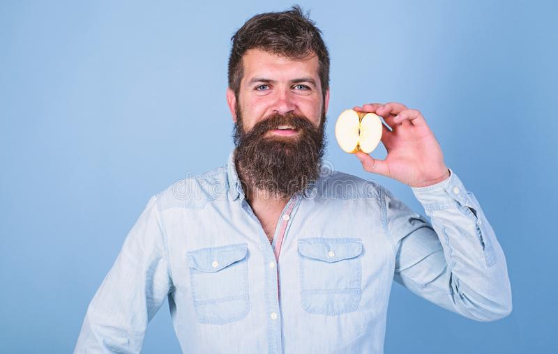 Man bearded smiling holds apple blue background. Half of apple healthy lifestyle. Nutritional value concept. Healthcare. Dieting vitamin nutrition. Hipster stock photos