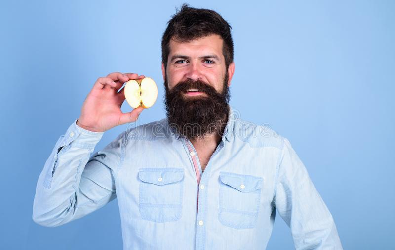 Man bearded smiling holds apple blue background. Half of apple healthy lifestyle. Nutritional value concept. Healthcare. Dieting vitamin nutrition. Hipster stock image