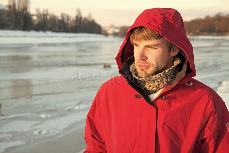 Man bearded stand warm jacket snowy nature background. Wind resistant clothes. Winter menswear. Clothes for winter walks. Hipster winter warm outfit. Guy wear royalty free stock image