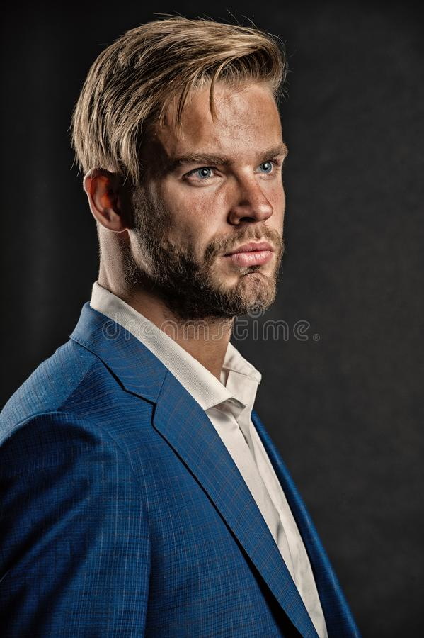 Man bearded strict face with hairstyle, dark background. Masculinity concept. Businessman attractive cares about royalty free stock photo