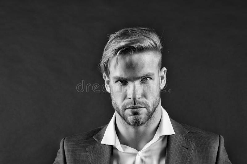 Man bearded strict face with hairstyle, dark background. Masculinity concept. Man bearded unshaven guy looks handsome royalty free stock photos