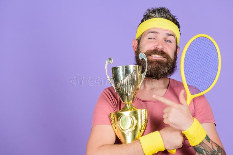 Man bearded successful athlete. First place. Sport achievement. Tennis champion. Win tennis game. Celebrate victory. Athletic man hold tennis racket and golden stock image