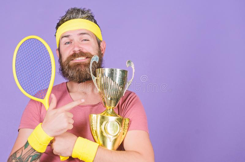 Man bearded successful athlete. First place. Sport achievement. Tennis champion. Win tennis game. Celebrate victory. Athletic man hold tennis racket and golden stock photos