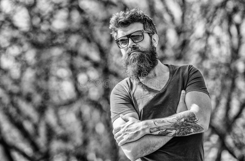 Man bearded with sunglasses nature background. Bearded hipster brutal man wear protective sunglasses. Hipster confident stock images