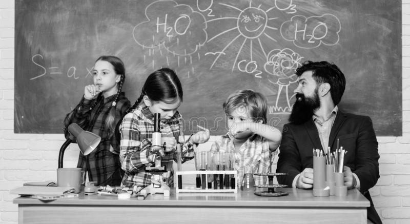 Man bearded teacher and pupils with test tubes in classroom. School chemistry lab. Science involves theory. School royalty free stock photo