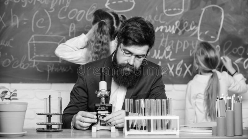 Man bearded teacher work with microscope and test tubes in biology classroom. Explaining biology to children. Biology stock photography
