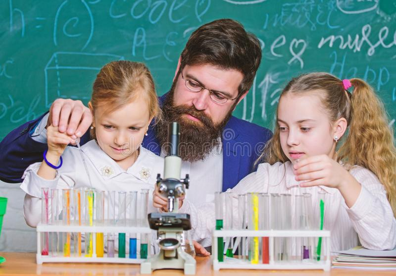 Man bearded teacher work with microscope and test tubes in biology classroom. How to interest children study. Explaining stock images