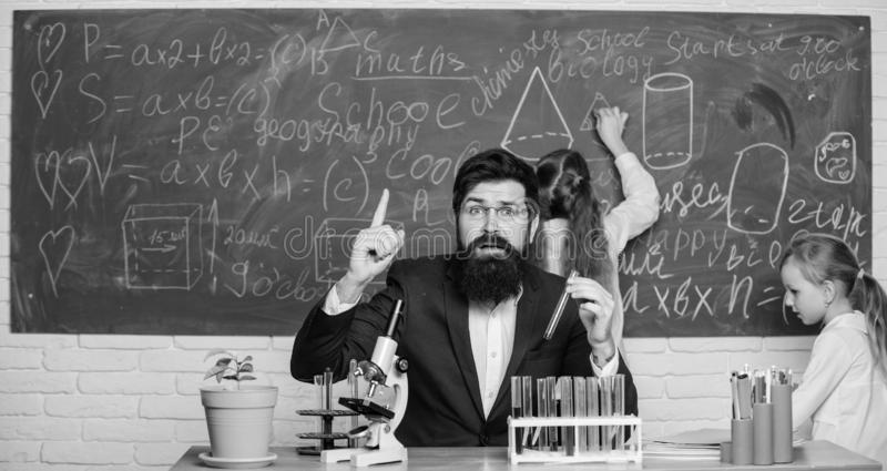Man bearded teacher work with microscope and test tubes in biology classroom. School teacher of biology. Explaining royalty free stock images