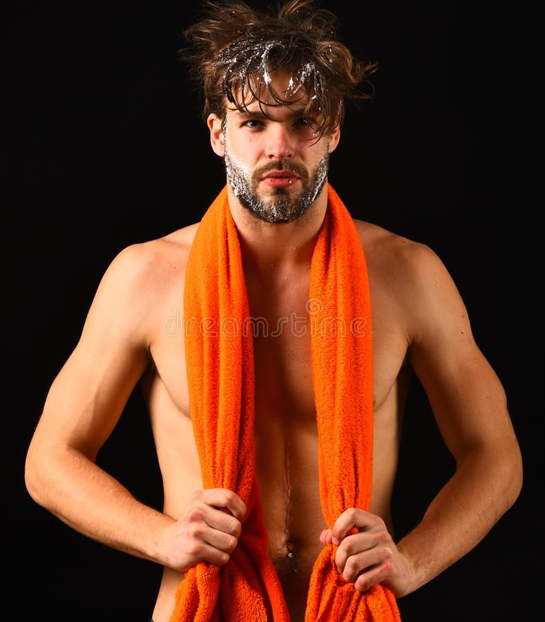 Man bearded tousled hair covered with foam or soap suds. Wash off foam with water carefully. Body care. Man with orange. Towel on neck ready to take shower royalty free stock photos