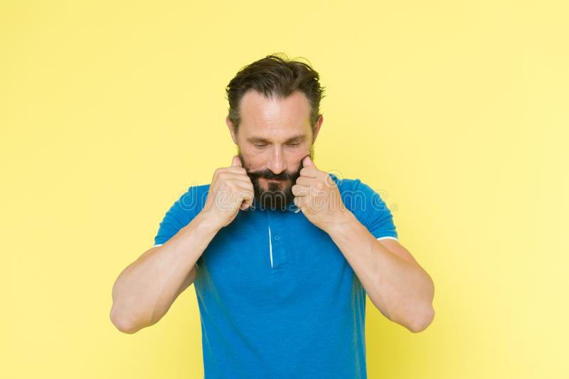 Man bearded twisting moustache yellow background. Ultimate moustache grooming guide. Hipster handsome mature thoughtful. Guy. Expert tips for growing and royalty free stock images