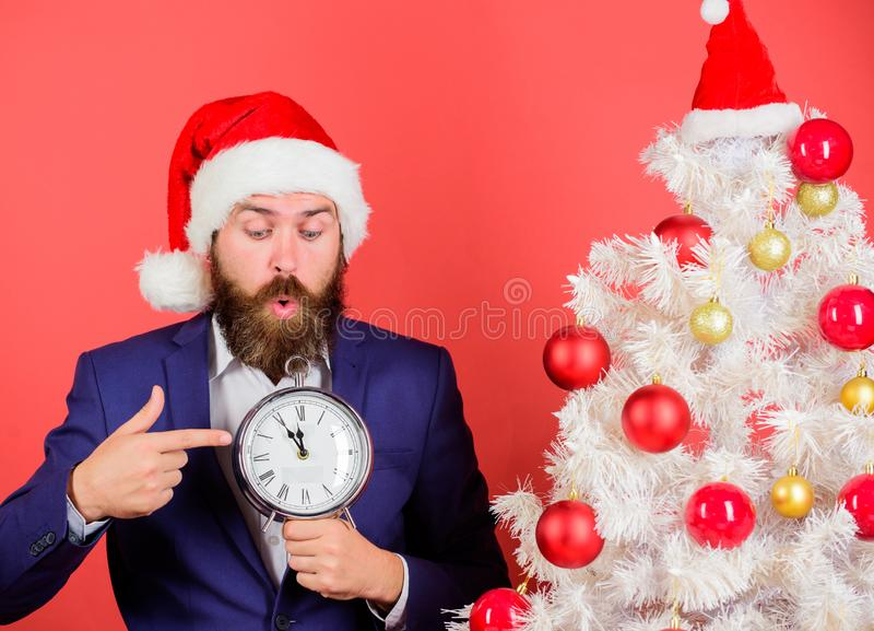 Man bearded wear suit and santa hat hold clock. Last minute deals. Counting time till christmas. How much time left royalty free stock photo
