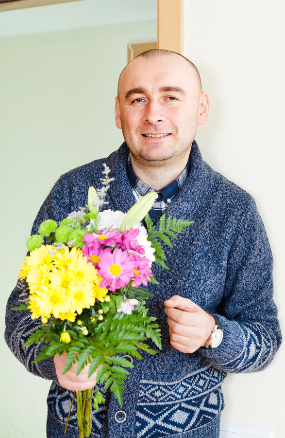 Man with beautiful bouquet. Man asks forgiveness with bouquet of flowers royalty free stock photography