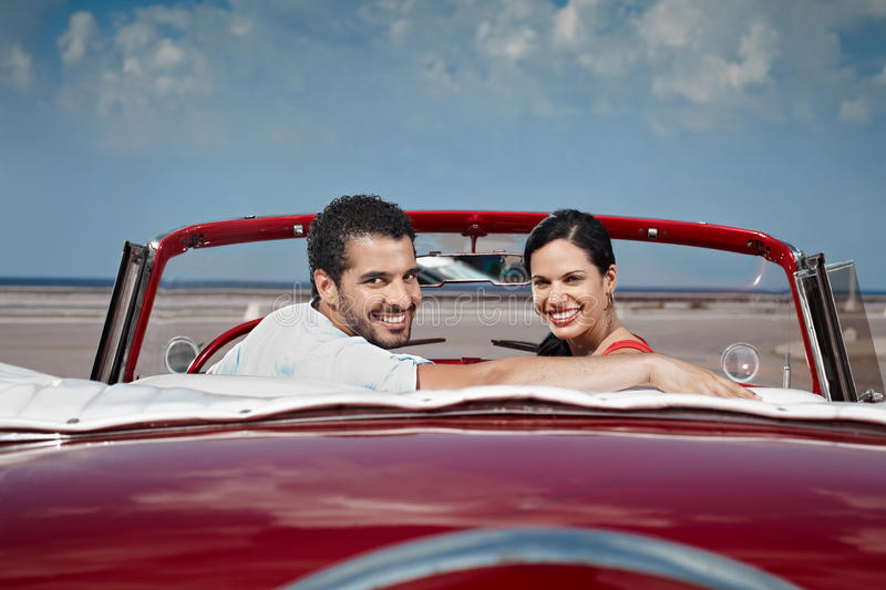 Man and beautiful woman hugging in cabriolet car. Boyfriend and girlfriend sitting in vintage car and hugging in havana, cuba. Horizontal shape, side view, copy royalty free stock images