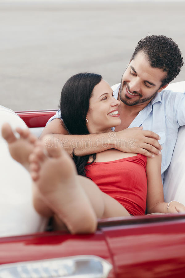 Man and beautiful woman hugging in cabriolet car. Boyfriend and girlfriend lying inside vintage convertible car and hugging. Vertical shape, front view, copy stock photo