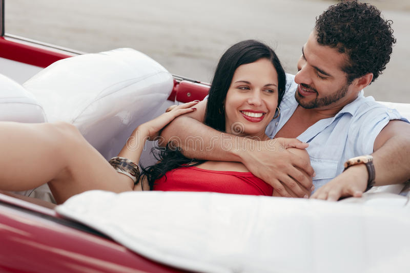Man and beautiful woman hugging in cabriolet car. Boyfriend and girlfriend lying inside vintage convertible car and hugging. Horizontal shape, side view stock image