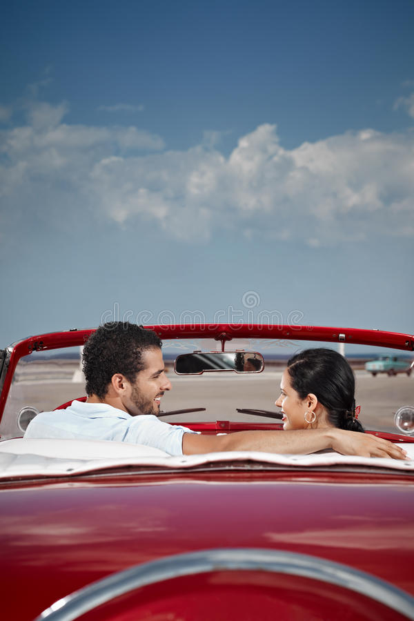 Man and beautiful woman hugging in cabriolet car. Boyfriend and girlfriend sitting in vintage car and hugging in havana, cuba. Vertical shape, rear view, copy royalty free stock image