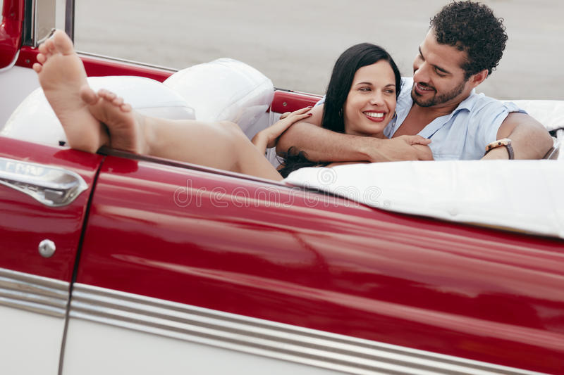 Man and beautiful woman hugging in cabriolet car. Boyfriend and girlfriend lying inside vintage convertible car and hugging. Horizontal shape, full length, side royalty free stock image