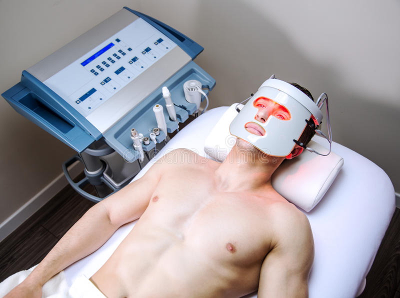 Man in a beauty clinic. Man in a clinic by becoming a beauty treatment stock image