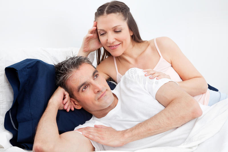 Man in bed turning away from woman stock image